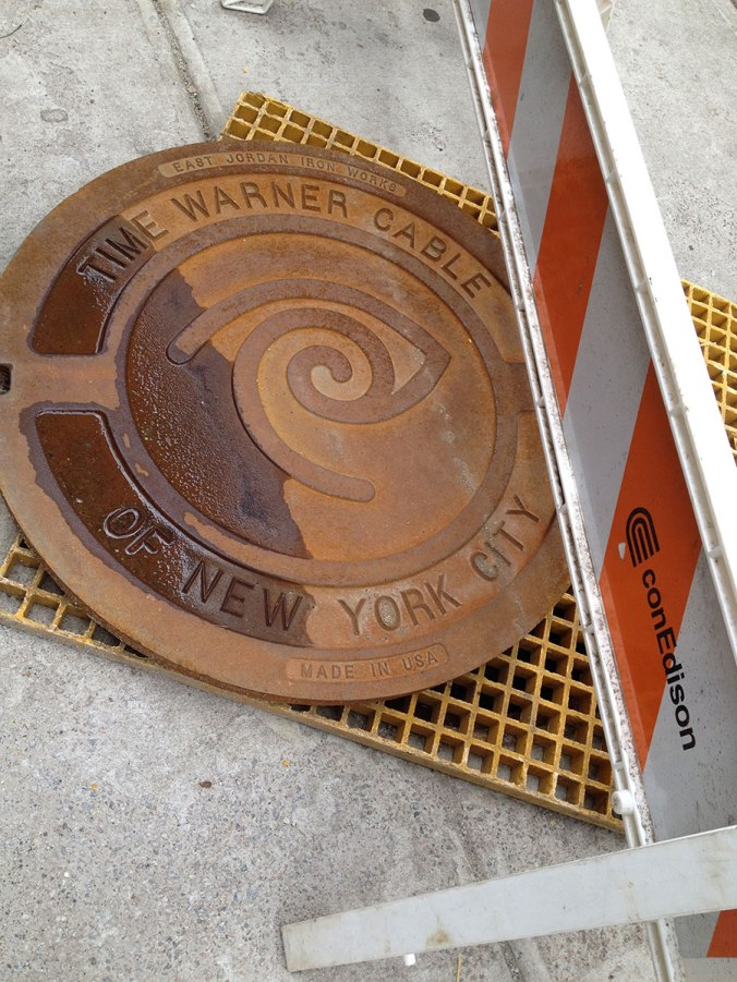 Time Warner manhole cover with Con Edison traffic barrier