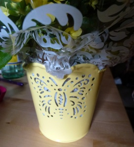 A pale yellow metal pot with a butterfly cutout