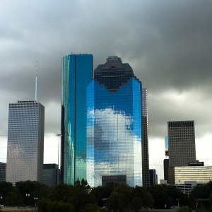 A building against a dark cloudy sky is reflecting a bright blue sky with white clouds