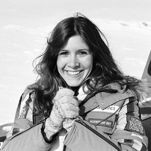 Black and white photo of Carrie Fisher, with wide smile and long unbound brunette hair, in snowy Norway, wearing a winter jacket and wooly knitted gloves