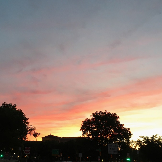Square photo of sunset clouds in colors of fuchsia, dark salmon, and bright gold over the crenellations of the Philadelphia